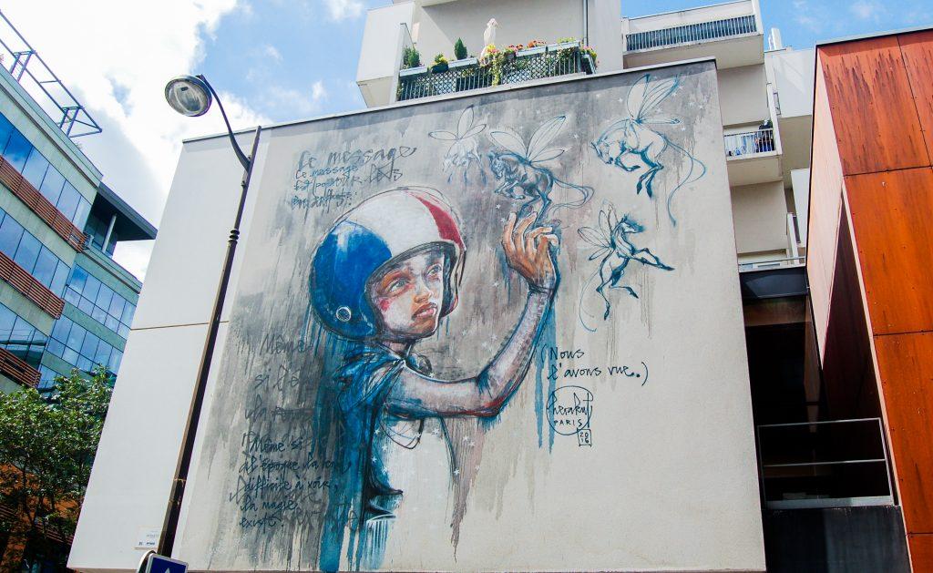 Fresque d'Herakut représentant un enfant avec un casque aux couleurs de la France, touchant le mur où apparaissent des chevaux ailés et un poème.
