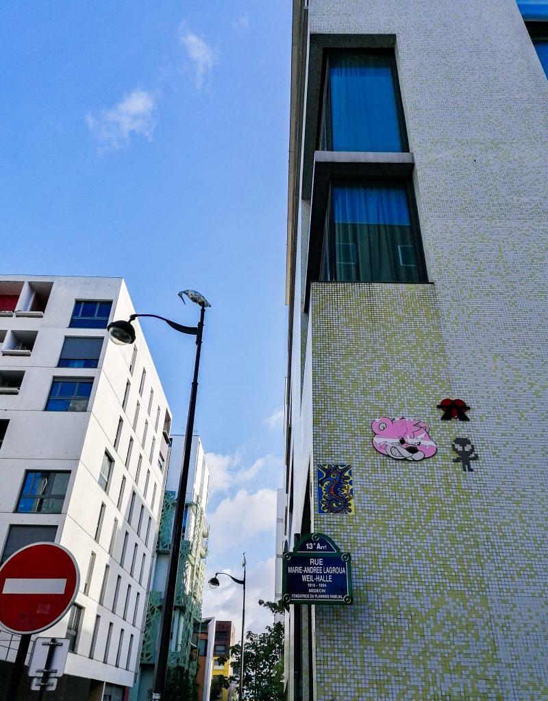 Vue de la rue avec plusieurs petites oeuvres dont des oiseaux en papiers aluminum perché au dessus des lampadaires, et des oeuvres collées à l'angle du mur
