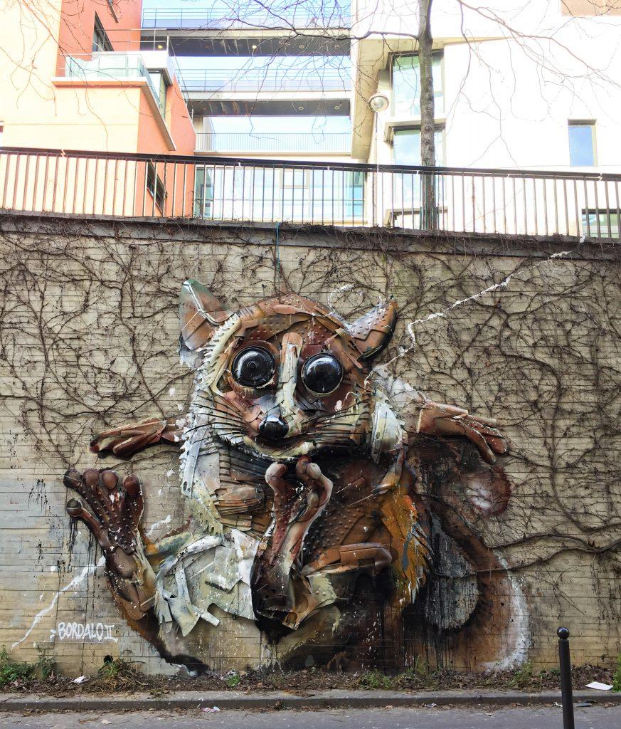 Fresque en relief de Bordalo Segundo représentant un lémurien, constitué d'objets plastique cloués au mur.