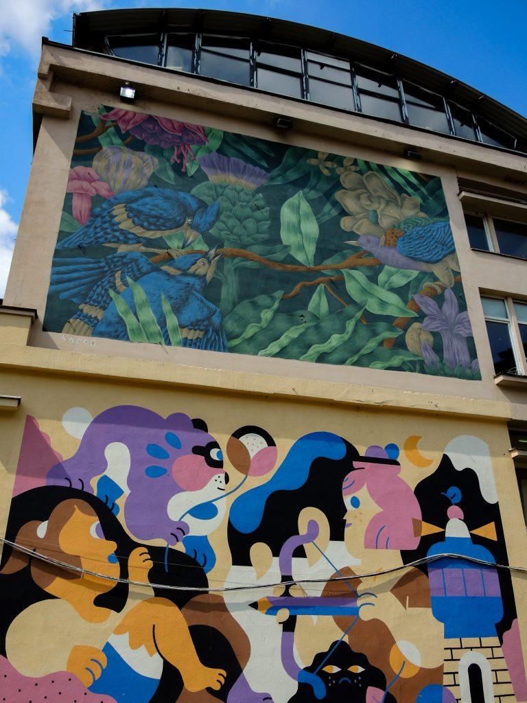 Deux fresques l'une au-dessus de l'autre, la première de Saddo représente un un paysage onirique de verdure et d'oiseau colorés ; la seconde d'Hedof représente des personnages enfantins dans un univers également très coloré.