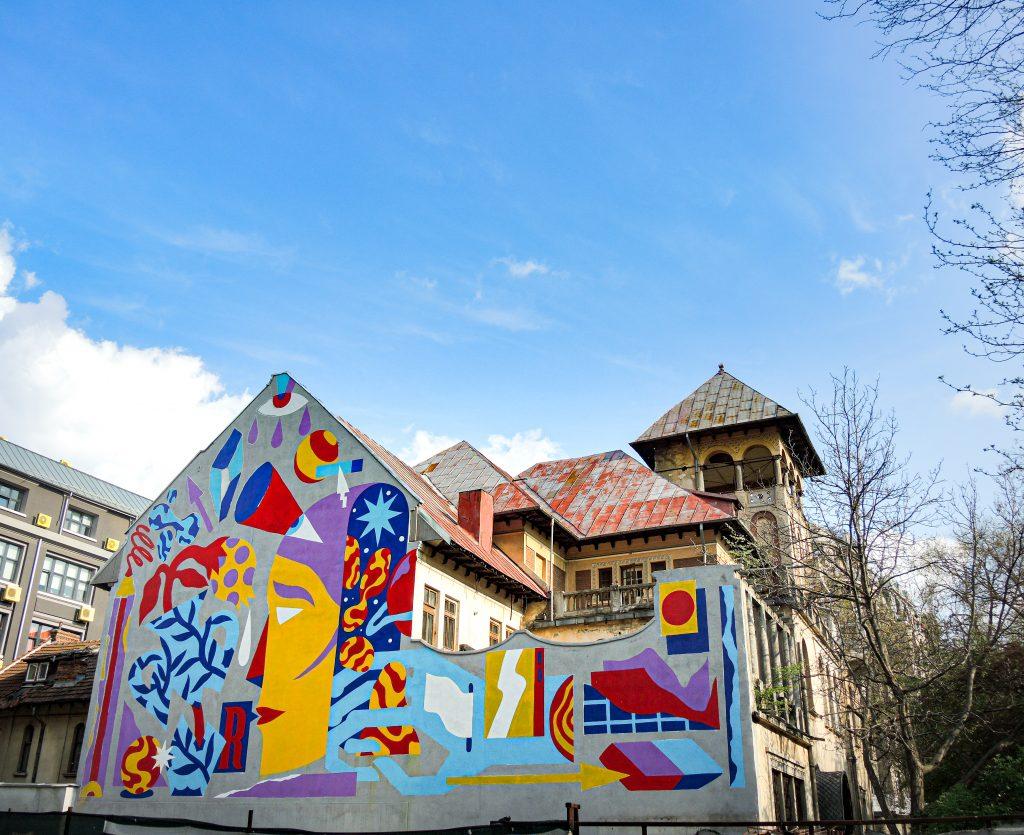 Fresque d'Akacorleone qui recouvre toute un mur sur le coté d'un grand bâtiment, représentant des formes et un visage assez cubiste tout en couleur