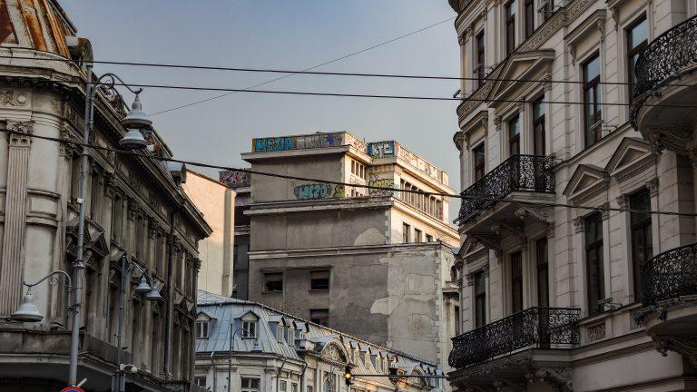 Vue d'une rue encadrée par des immeubles avec au bout de la rue des graffiti au dernier étage d'un autre bâtiment