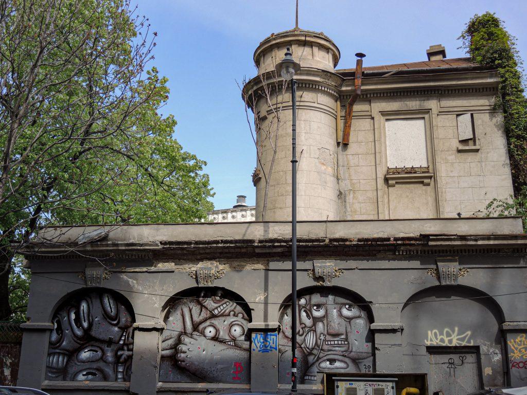 Des personnages se cachent dans les alcôves de ce qui étaient des fenêtres du premier étage d'un bâtiment
