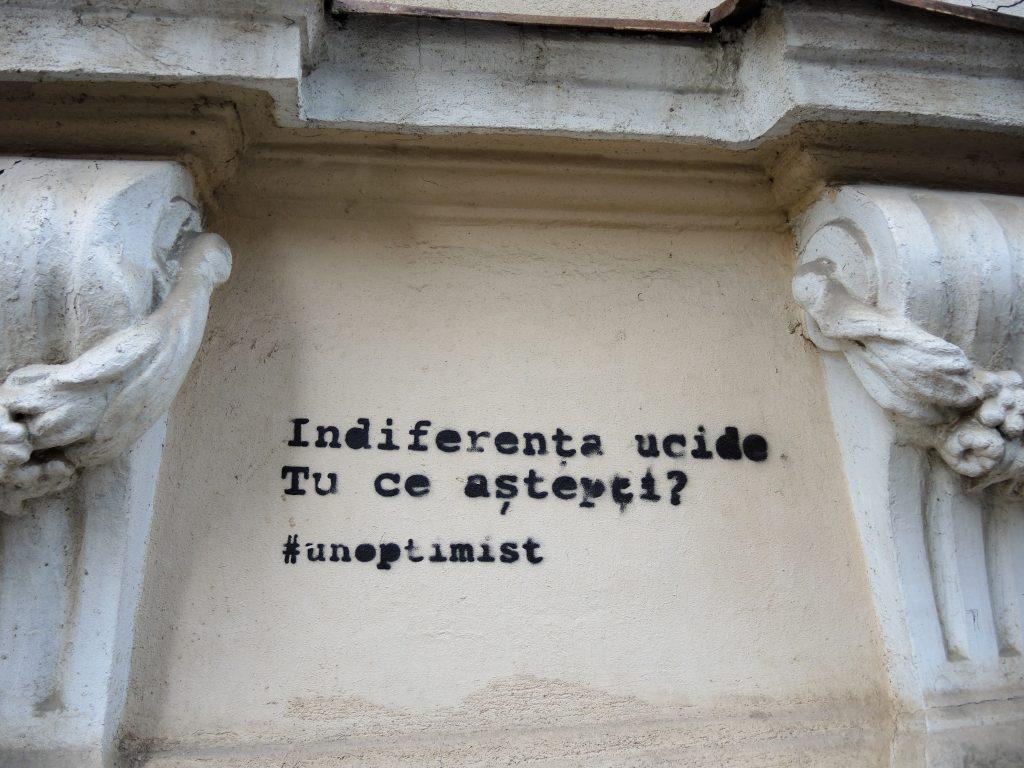 Texte en pochoir placé entre deux éléments de décors d'un immeuble