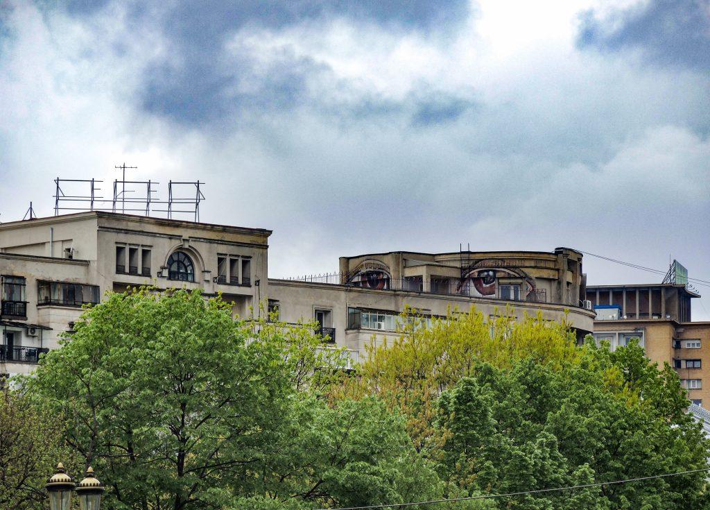 Deux grands yeux rouges se fondent dans le décors du haut d'un grand immeuble.