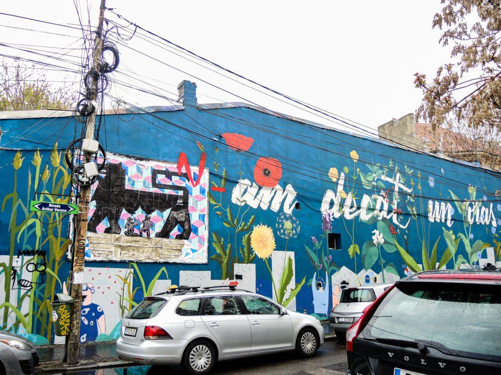 Longue fresque collaborative avec un message en roumain écrit tout du long et des fleurs et personnages ornent le bas du mur.