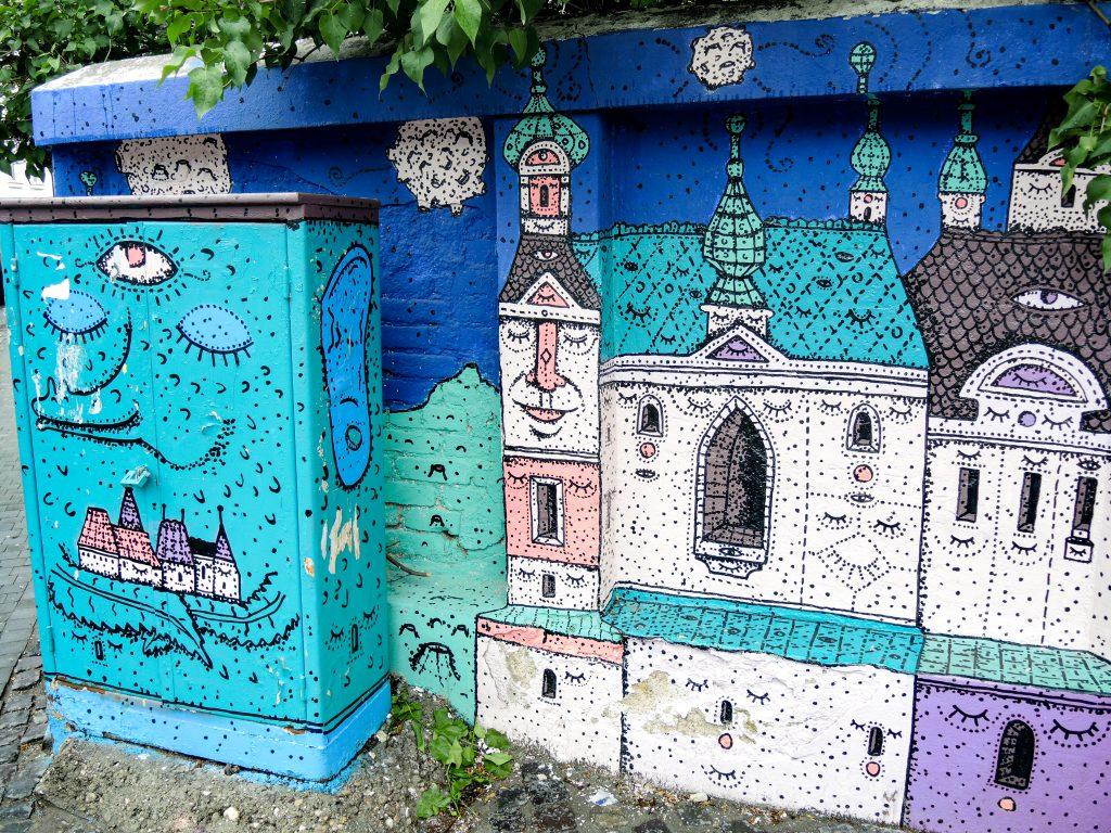 Fresque très coloré avec des immeubles animalisés dessinés en pointillé.