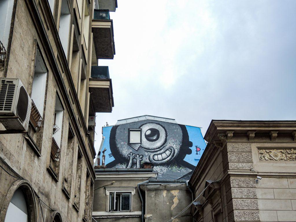Fresque de Patrata en piton d'immeuble représentant un personnage à tête ronde et à l'oeil unique, avec un livre